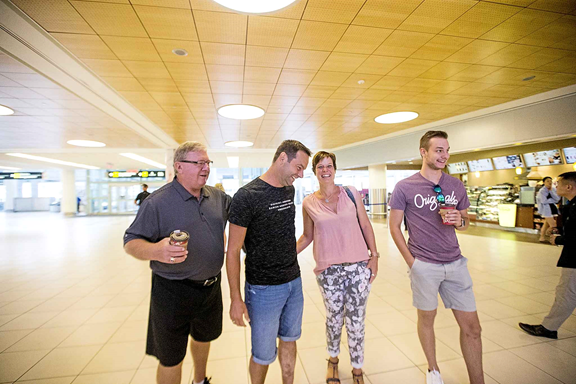 Jim Benzelock (left), Marco Kiunka, Nicole Kiunka, and Noah Kiunka wait for Jamie Benzelock to arrive the airport. (MIKAELA MACKENZIE / WINNIPEG FREE PRESS)